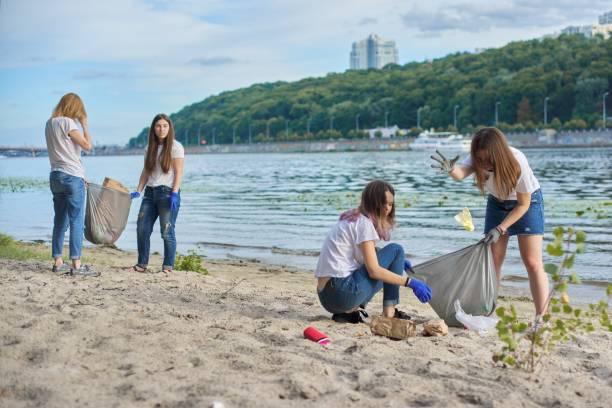 Gençler doğada plastik çöp temizleme, nehir kıyısı stok fotoğrafı