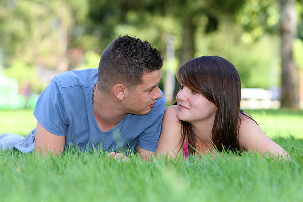 Teenagers couple Teen couple lying in the grass ecole stock pictures, royalty-free photos & images
