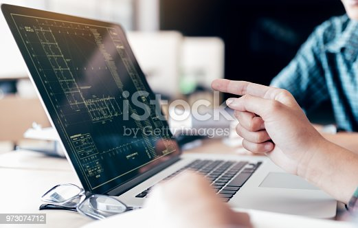 istock Teenagers develop programming with blueprint code in laptop monitor. 973074712