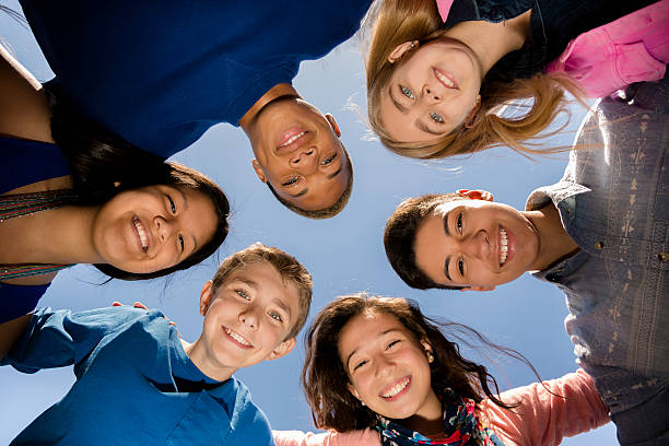 Teenagers: Diverse group of friends huddle outside together. Blue sky. Multi-ethnic group of teenage friends hang out, huddle together with arms around each other outdoors. Blue sky background.  12 13 years stock pictures, royalty-free photos & images