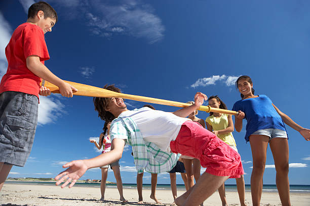 Teenagers doing limbo dance on beach stock photo