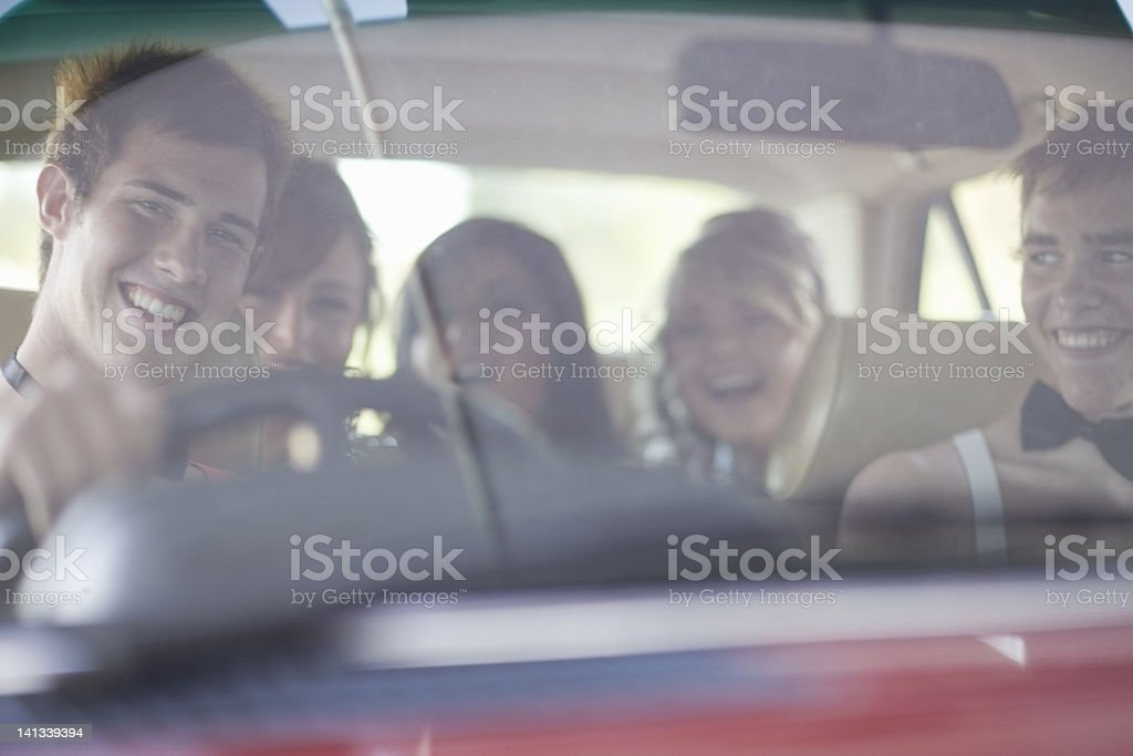 Teenagers driving in formal wear stock photo