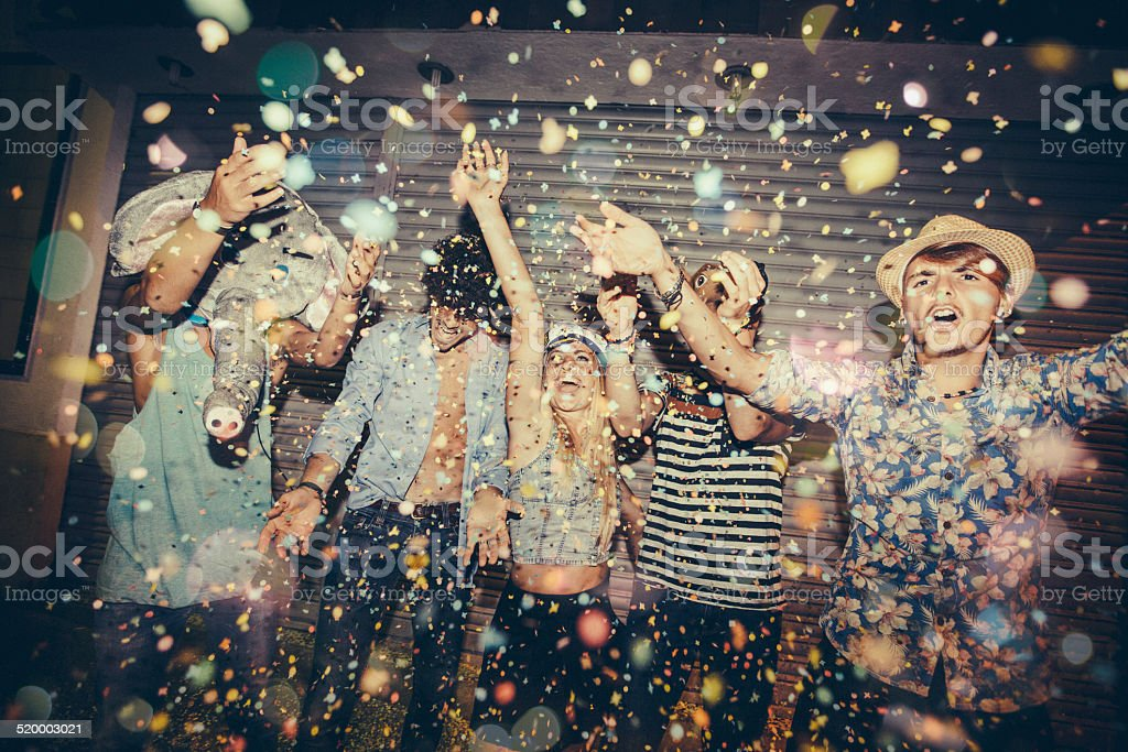 Teenagers Enjoying Confetti Whilst Partying In Street stock photo