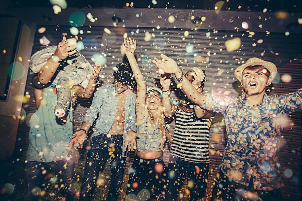 teenager genießen konfetti während party in street - freund kostüme stock-fotos und bilder