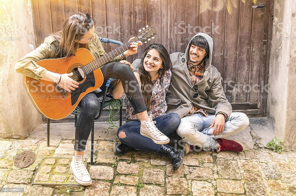 Teenagers friends having fun playing guitar outdoors stock photo