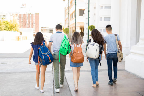 Teenagers going to school Rear view of group of five teenage boys ands girls walking out on city street with schools bags generation z stock pictures, royalty-free photos & images