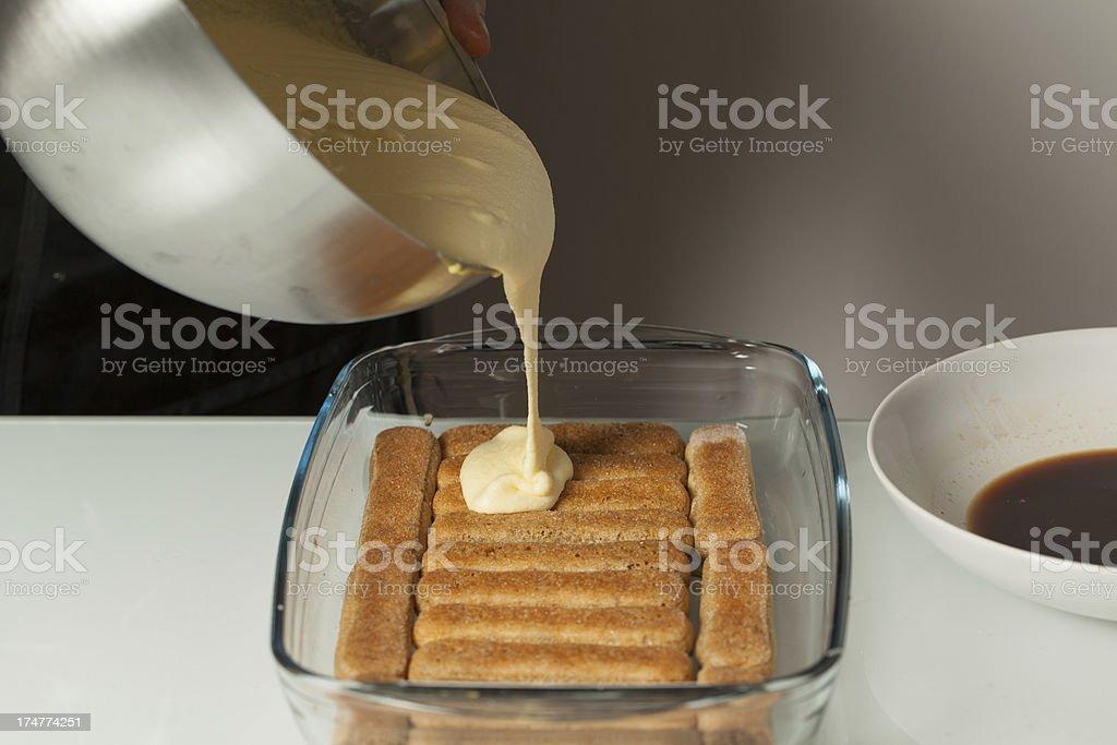 Teenager's Hand Pouring Cream for Tiramisu stock photo