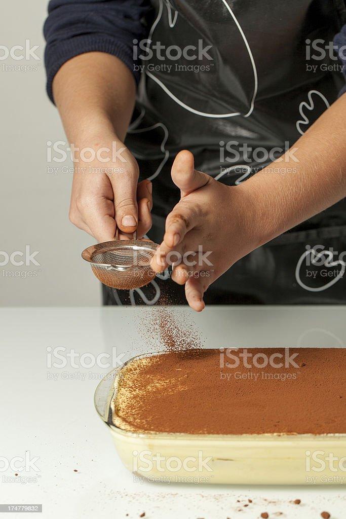 Adolescente mano versare il cioccolato in polvere su Tiramisù - foto stock
