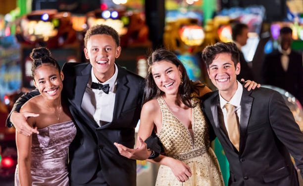 Teenagers having fun at prom A multi-ethnic group of four teenagers, two interracial couples, having fun at their high school prom. The two girls are wearing prom dresses and their dates are wearing a suit and tuxedo. prom night stock pictures, royalty-free photos & images