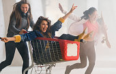 A group of teenagers having fun in an abandoned construction site burning smoke bombs and racing with a shopping cart, bicycle and skateboard