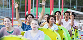 A multi-ethnic group of eight teenagers having fun riding a rollercoaster at an amusement park, smiling and laughing with their arms raised.