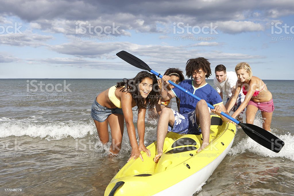 Teenagers helping their friend with his kayak royalty-free stock photo