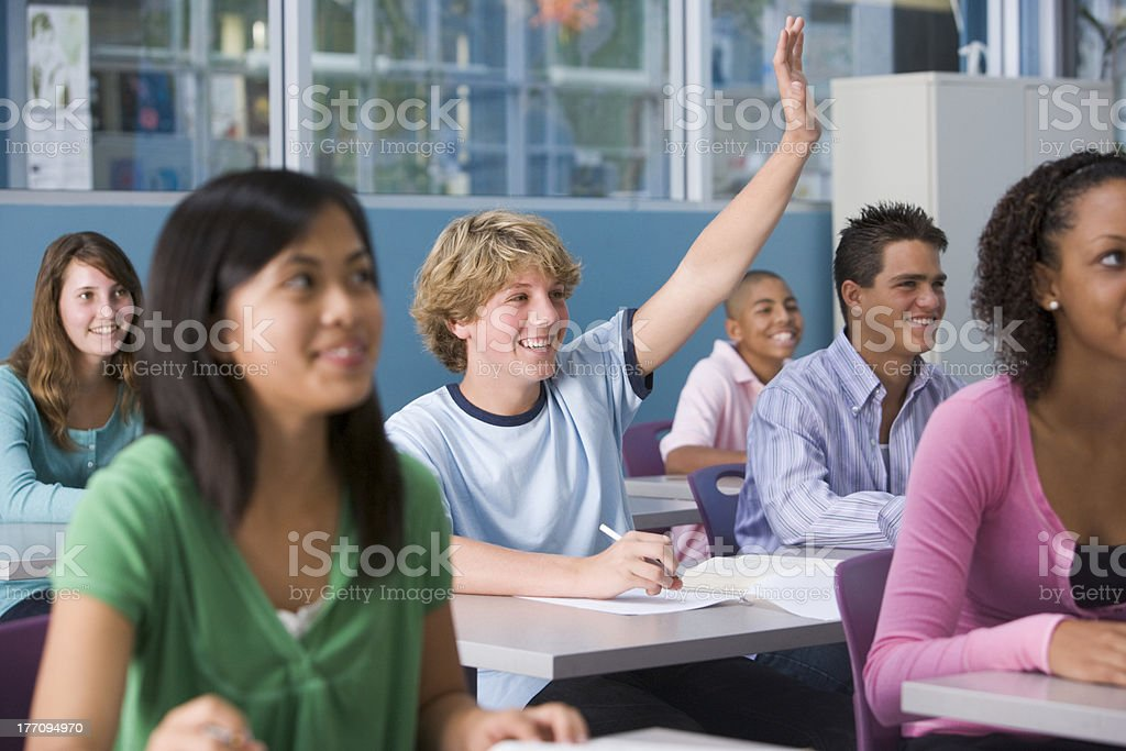 Teenagers in class, one with hand raised royalty-free stock photo