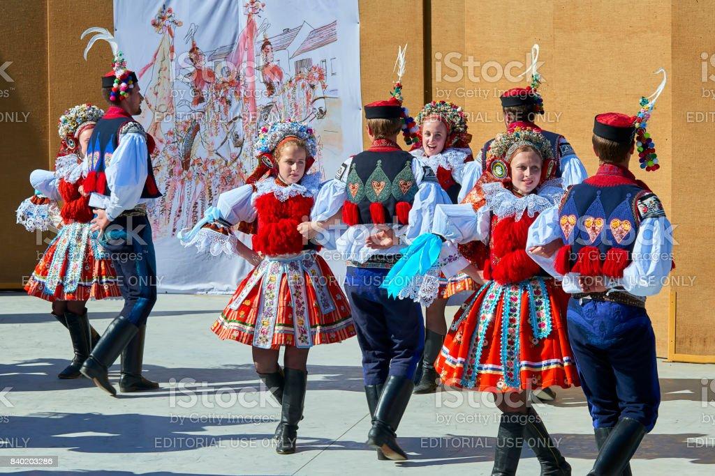 Boys and girls in folk dresses dance folk dance after parade during...