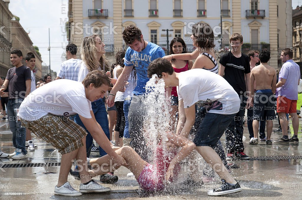 Teenagers in the fountain the last day of the school in Turin stock photo