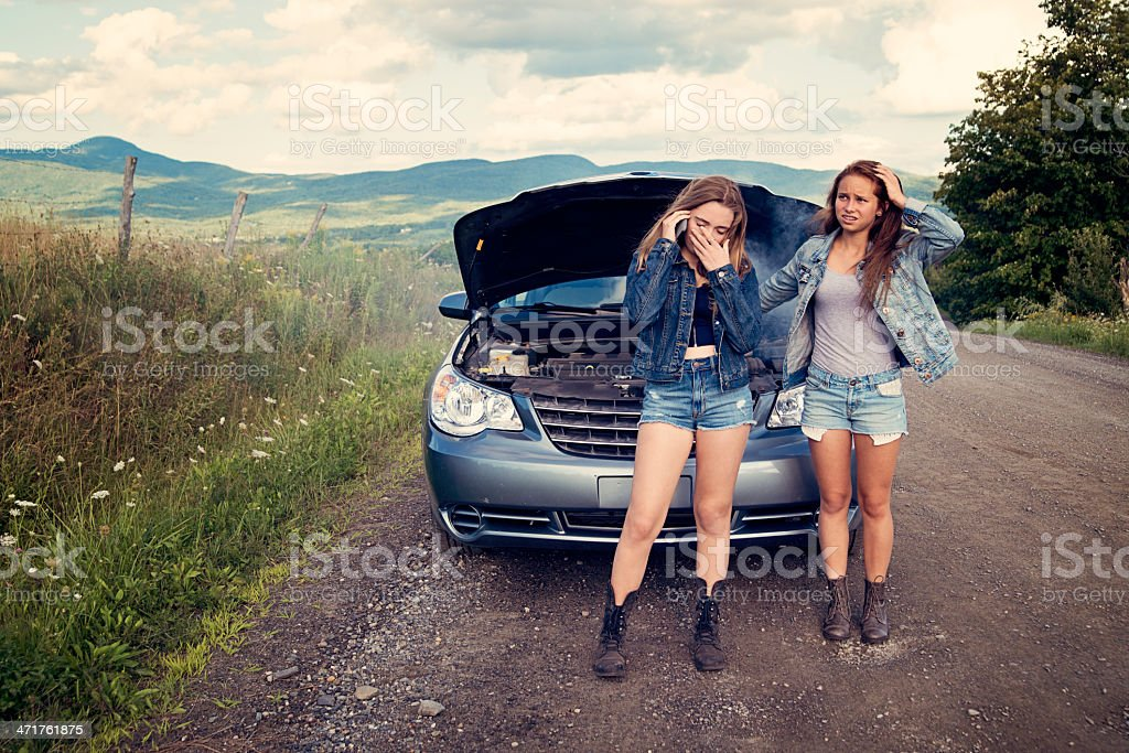 Teenagers in trouble on road with brokedown parent's car. stock photo
