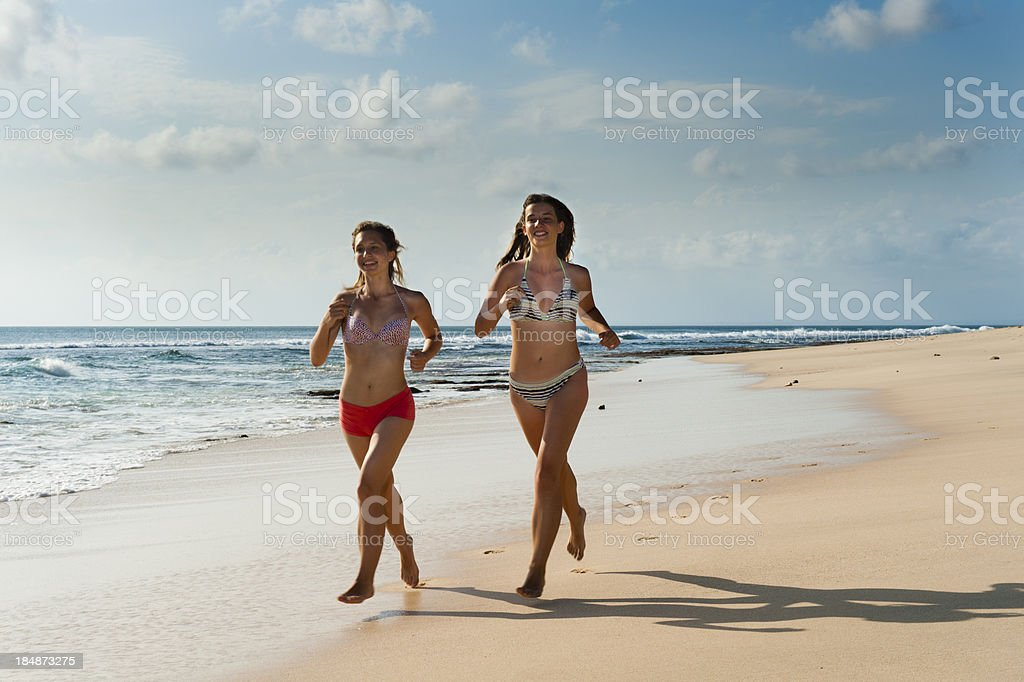 Teenagers jogging on the sandy beach stock photo