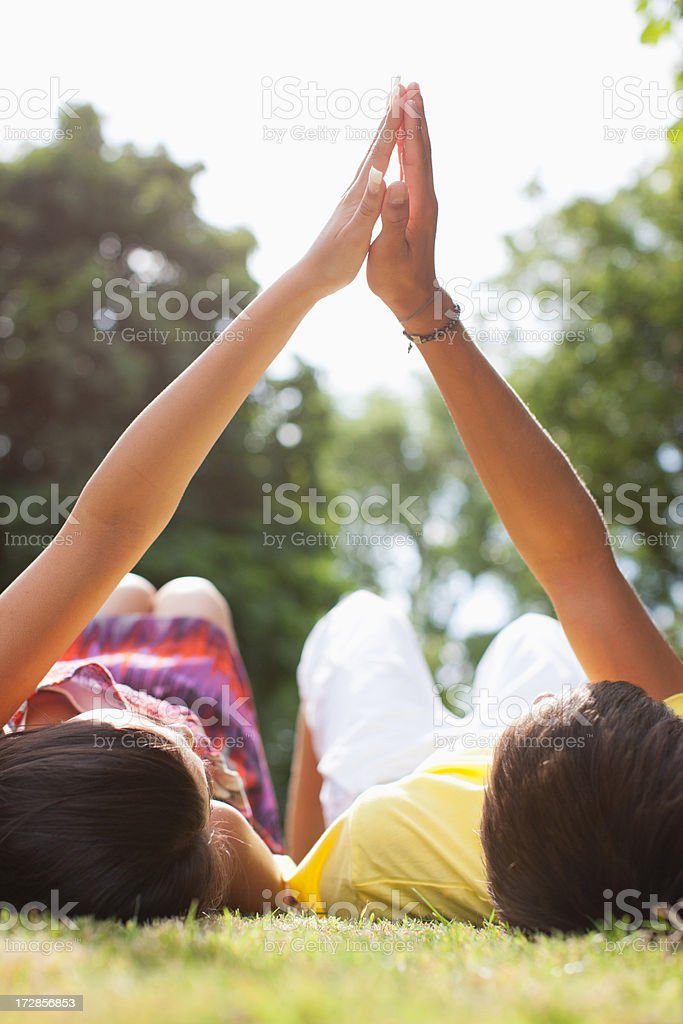 Teenagers laying in grass holding hands stock photo