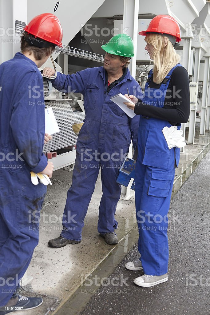 Teenagers learning a occupation. Trainee looking at motor. stock photo