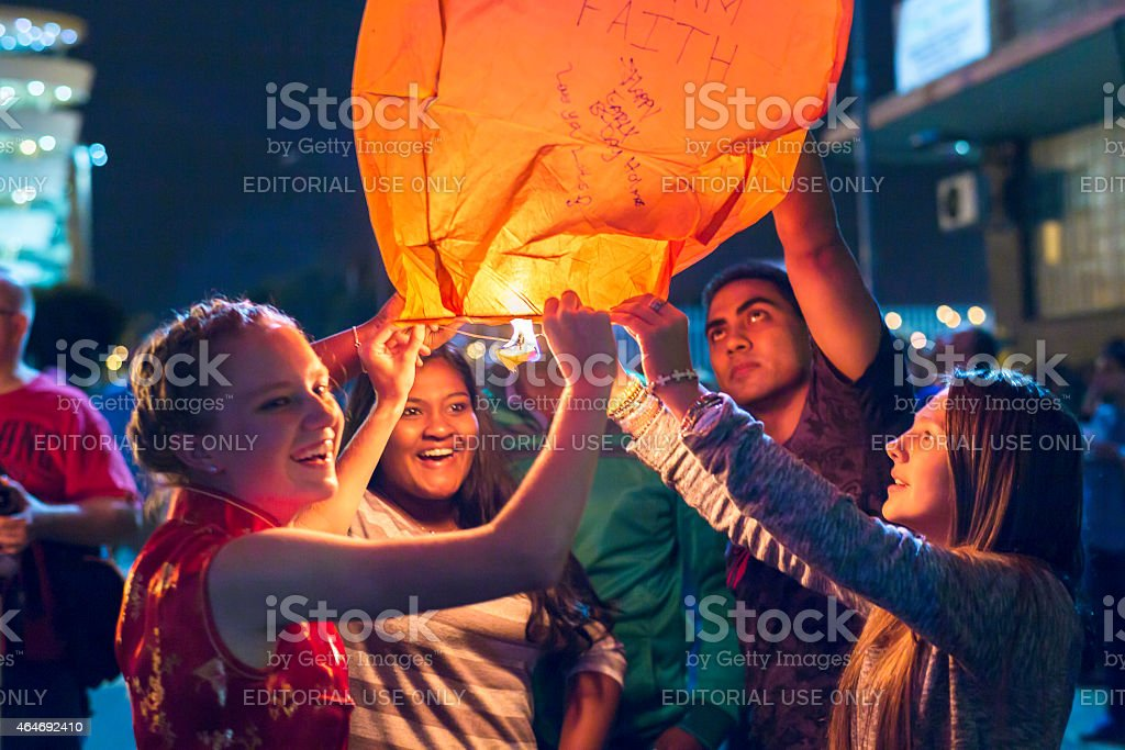 Teenagers lighting up a chinese sky lantern stock photo