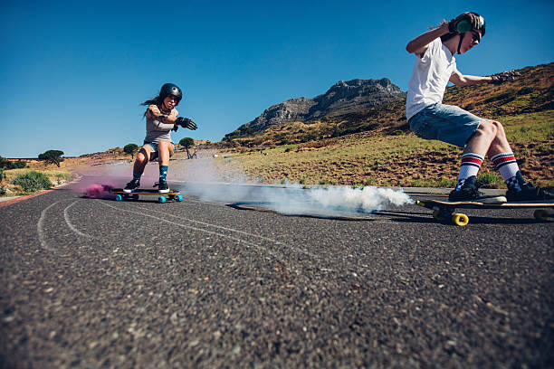 Teenagers longboarding on open road stock photo