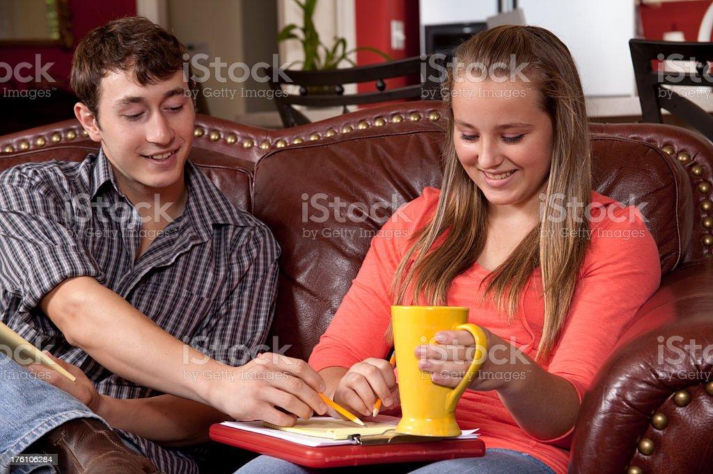 Teenagers on sofa doing homework royalty-free stock photo