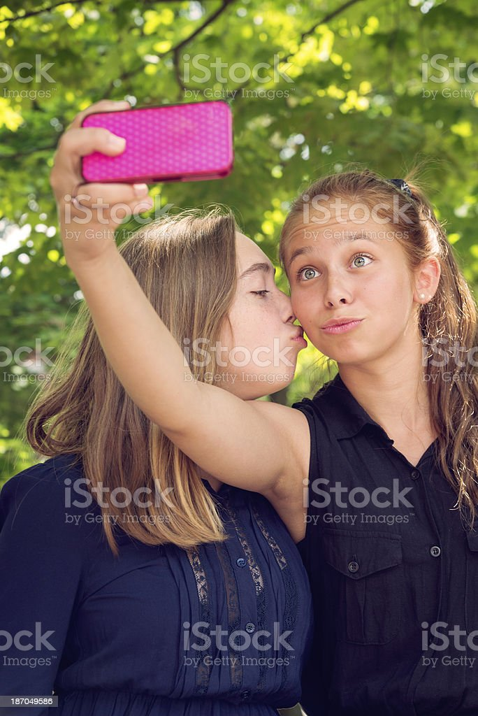 Teenagers photographing themselves on mobile phone. royalty-free stock photo