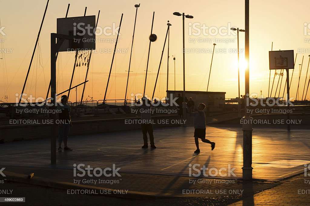 Teenagers playing basketball at sunrise in Brighton, UK royalty-free stock photo