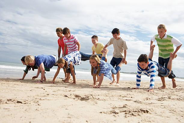 Jugendliche spielen am Strand – Foto