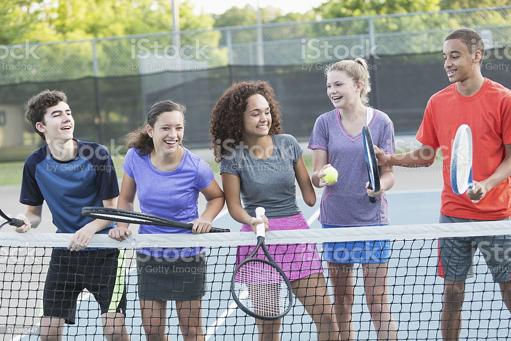 Teenagers playing tennis stock photo