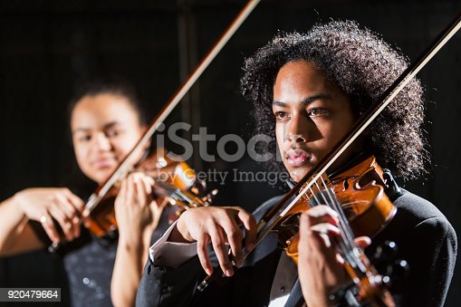 Two mixed race teenagers performing together in a concert, playing violins on stage. The 15 year old girl is Hispanic, black and Caucasian. The focus is on the boy, 16, who is Hispanic, Asian and African-American.