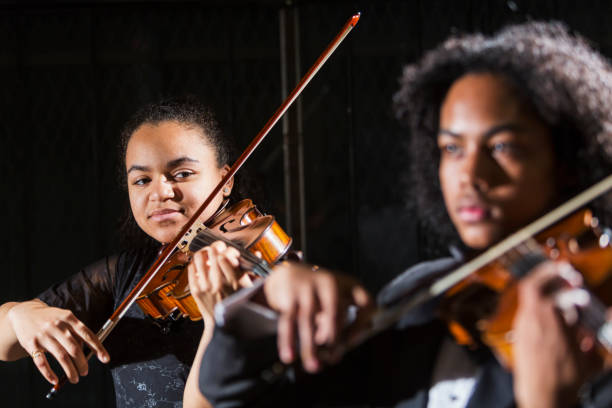 Teenagers playing violins in concert, focus on girl Two mixed race teenagers performing together in a concert, playing violins on stage. The focus is on the 15 year old girl who is Hispanic, black and Caucasian. The boy, 16, is Hispanic, Asian and African-American. child prodigy stock pictures, royalty-free photos & images