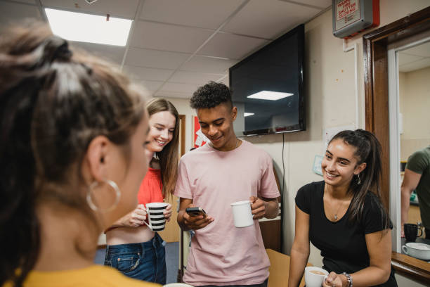 Teenagers Relaxing at Youth Club Small group of teenagers are talking and enjoying cups of tea at youth club. The boy is using his smart phone. community center stock pictures, royalty-free photos & images