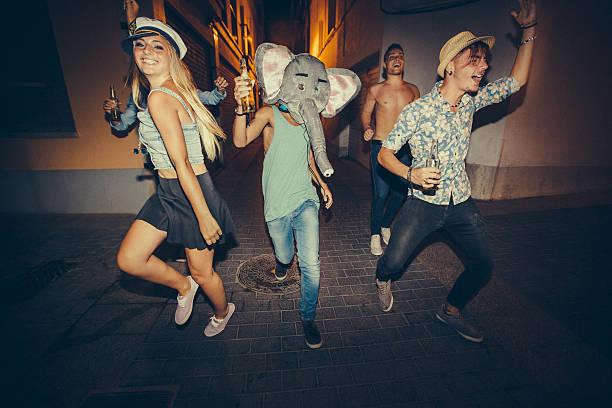 teenager läuft auf straße bei nacht party - bier kostüm stock-fotos und bilder