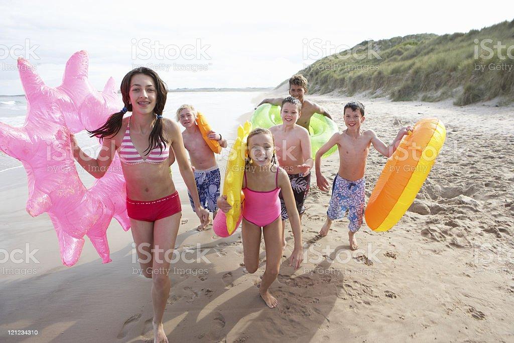 Teenagers running on beach royalty-free stock photo