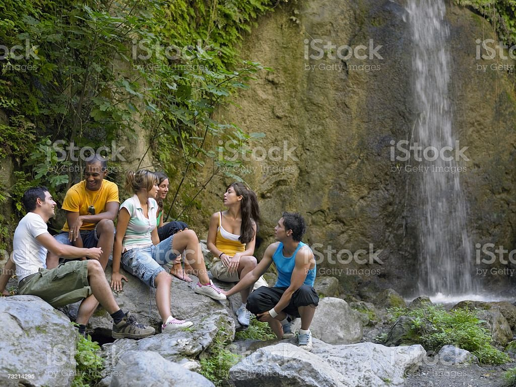 Teenagers sat next to waterfall royalty-free stock photo