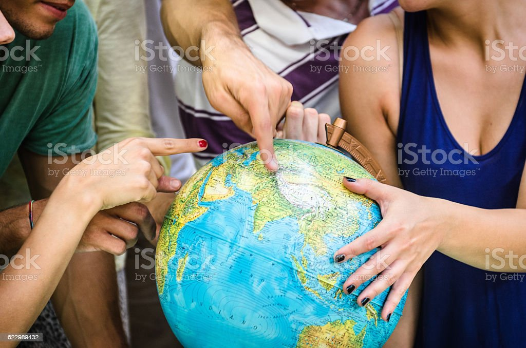 teenagers searching place on a globe