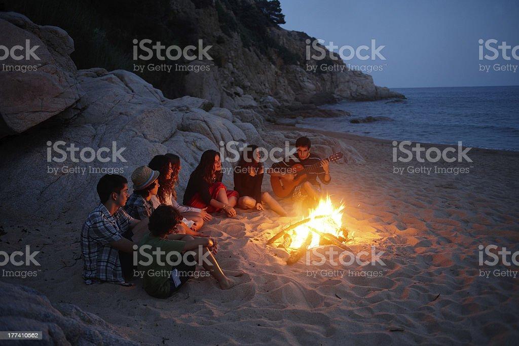 Teenager singen um ein Feuer im beach – Foto