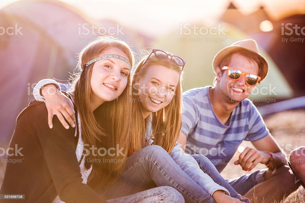 Teenagers sitting on the ground in front of tents royalty-free stock photo
