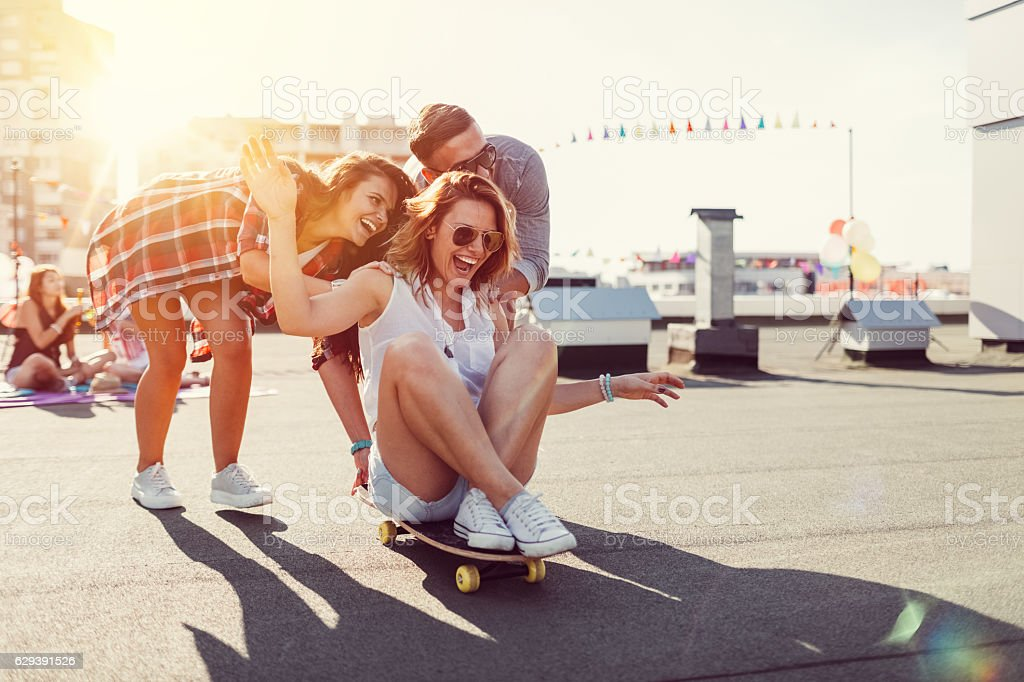 Teenagers skateboarding on rooftop terrace stock photo