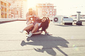 Girls having fun with skateboard on the rooftop