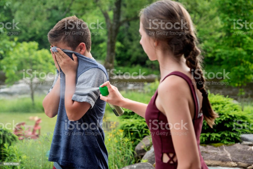 Teenagers spraying insect repellant on each other in summer nature. stock photo