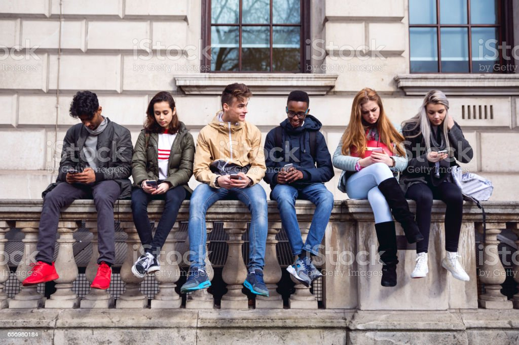 Teenagers students using smartphone on a school break - Royalty-free 18-19 Years Stock Photo
