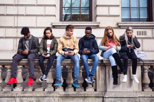 jugendliche schüler mit smartphone auf eine schule pause - jugendalter stock-fotos und bilder
