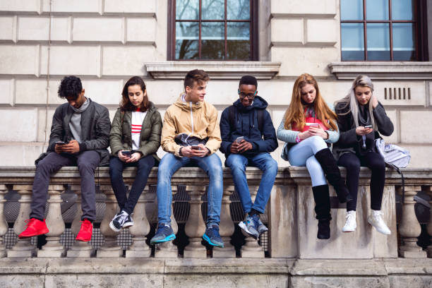 teenagers students using smartphone on a school break - street fashion stock photos and pictures