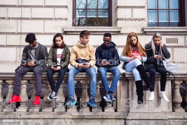 Teenagers Students Using Smartphone On A School Break Stock Photo - Download Image Now