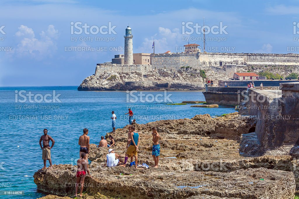 Teenagers swimming  near Moro castle stock photo