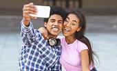 Teenagers taking selfie having fun and grimacing