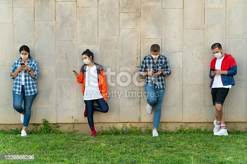 Teenagers texting mobile phone messages leaning on urban wall