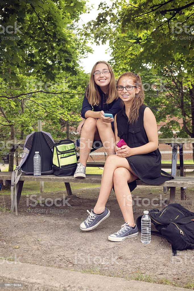 Teenagers texting sitting on a bench front of high school. royalty-free stock photo